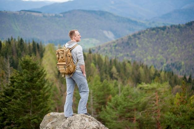 Mâle grimpeur avec sac à dos brun sur le sommet du rocher