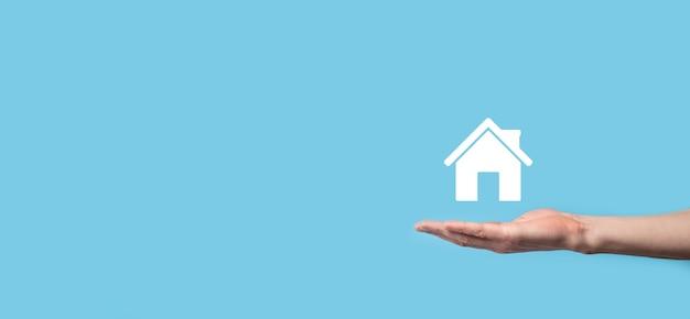 Mâle main affichant l'icône de la maison sur fond bleu.