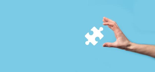 Mâle main affichant l'icône de puzzle sur fond bleu.