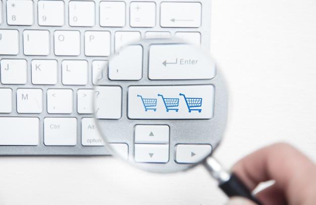 Mâle main à l'aide de la loupe. caddies sur clavier d'ordinateur. shopping en ligne