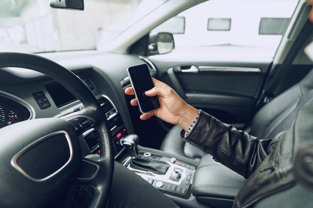 Mâle main à l'aide de smartphone assis dans une voiture