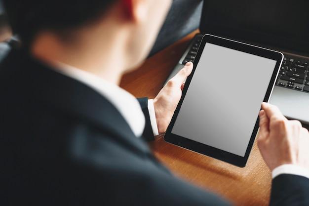 Mâle main à l'aide d'une tablette assis à un bureau avec un ordinateur portable sur le bureau.