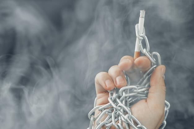 Mâle main dans des chaînes métalliques tenant cigarette, dépendance au tabagisme