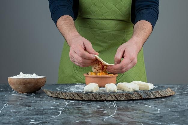 Mâle main dans des gants faisant de la nourriture sur une table en marbre.