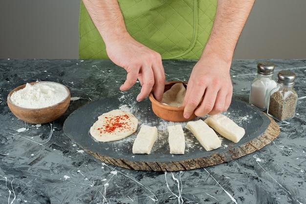 Mâle main dans des gants faisant de la pâte sur une table en marbre.