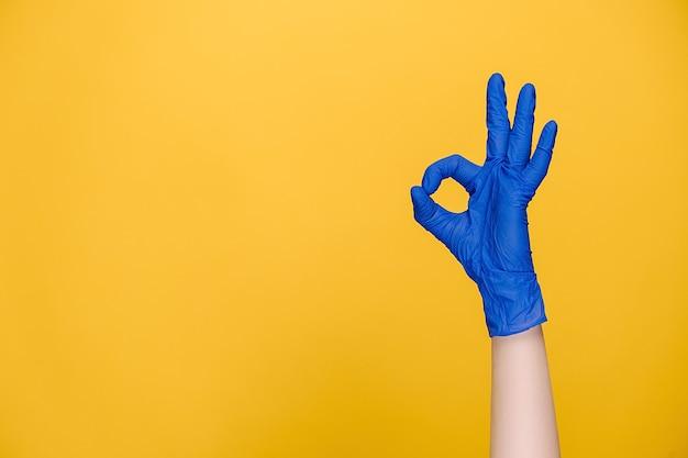 Mâle main dans des gants médicaux montre signe ok