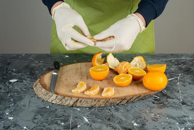 Mâle main dans des gants tenant des segments de mandarine sur la table.