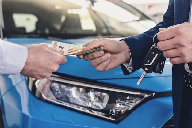 Mâle main donnant des billets en euros pour le concessionnaire close up