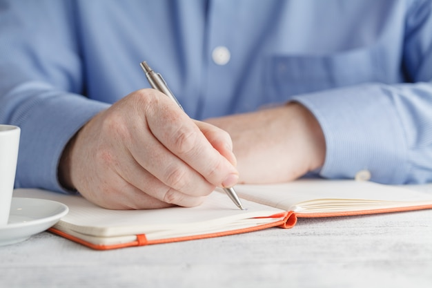 Mâle main écrit dans un cahier avec un stylo