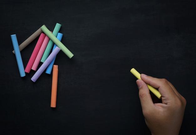 Mâle main écrivant sur tableau noir vide et espace de copie de craie colorée