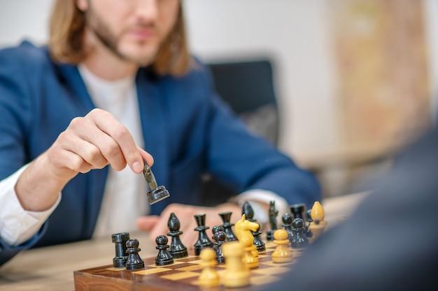 Mâle main d'un joueur avec pièce d'échecs noire au-dessus du plateau pendant le jeu