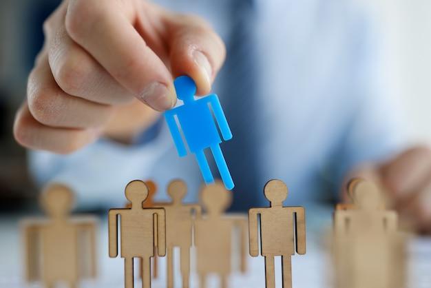 Mâle main mettant l'homme jouet bleu en bois. concept de gestion des ressources humaines