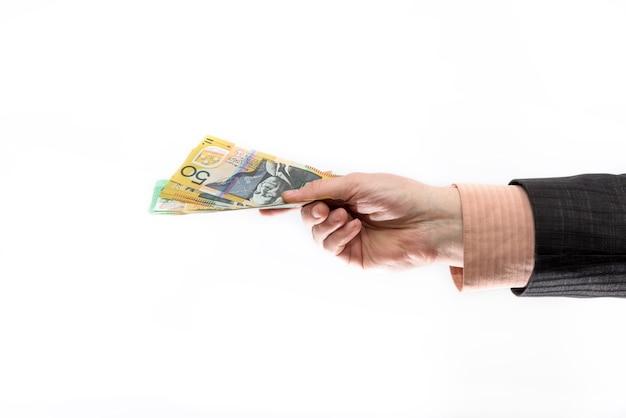 Mâle main offrant des billets en dollars australiens isolés