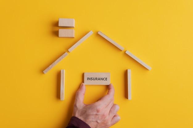 Mâle main plaçant une carte en bois avec signe d'assurance dessus dans une maison faite de blocs de bois
