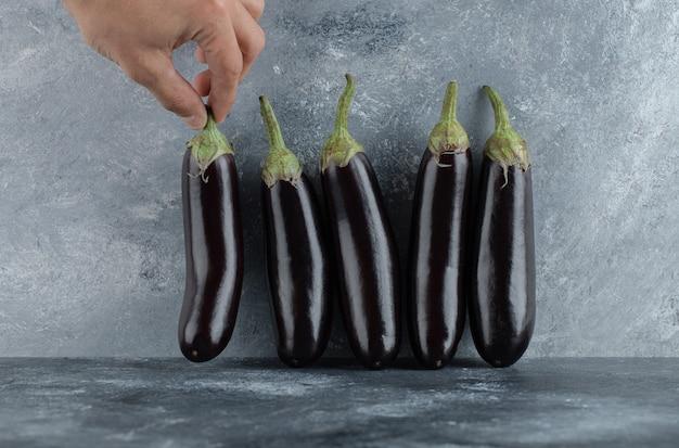 Mâle main prenant l'aubergine de ligne.