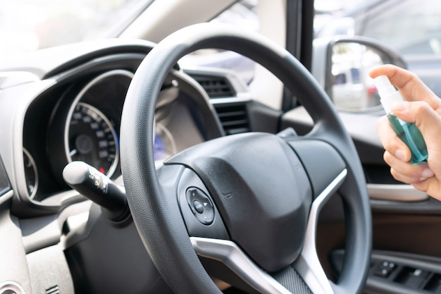 Mâle main pulvérisant de l'alcool sur le volant de voiture pour la désinfection.