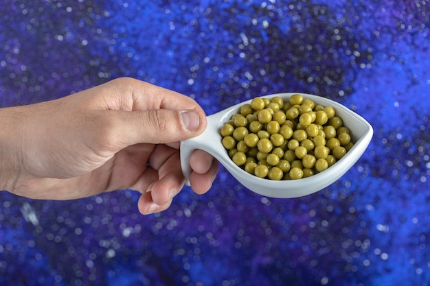Mâle main tenant un bol de pois verts