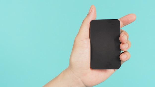 Mâle main tenant une carte vierge noire isolée sur fond vert menthe ou bleu tiffany.