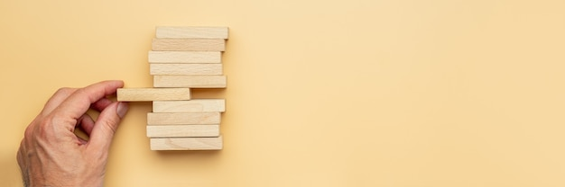 Mâle main tenant la cheville en bois du milieu dans une pile d'entre eux dans une image conceptuelle. sur fond jaune avec espace de copie.
