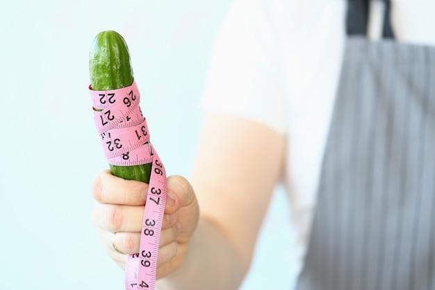 Mâle main tenant le concombre enveloppé dans un ruban à mesurer