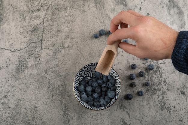 Mâle main tenant une cuillère sur le dessus du bol de bleuets