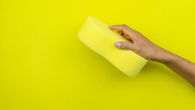 Mâle main tenant une éponge sur jaune.
