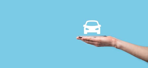 Mâle main tenant l'icône automatique de voiture sur fond bleu. composition de la bannière large assurances automobiles et concepts de dispense de dommages par collision.
