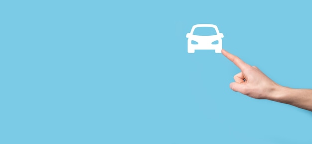 Mâle main tenant l'icône automatique de voiture sur la surface bleue