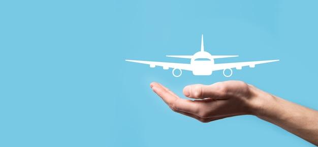 Mâle main tenant l'icône d'avion avion sur bleu