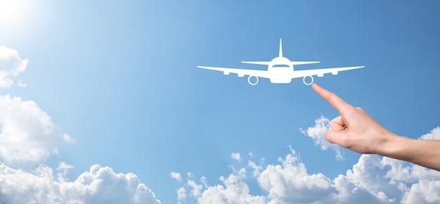 Mâle main tenant l'icône d'avion avion sur fond bleu. achat de billets banner.nline.icônes de voyage sur la planification de voyage, le transport, l'hôtel, le vol et le passeport.concept de réservation de billets d'avion.
