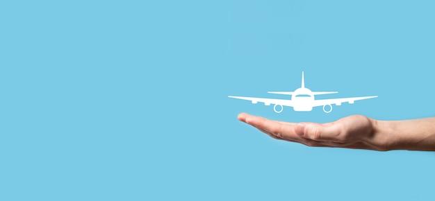 Mâle main tenant l'icône d'avion avion sur fond bleu.