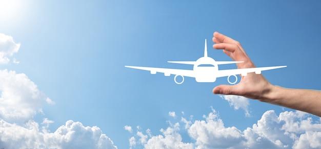 Mâle main tenant l'icône d'avion avion sur la surface bleue
