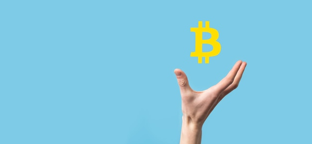 Mâle main tenant une icône bitcoin sur fond bleu. bitcoin cryptocurrency digital bit coin btc monnaie technology business internet concept.