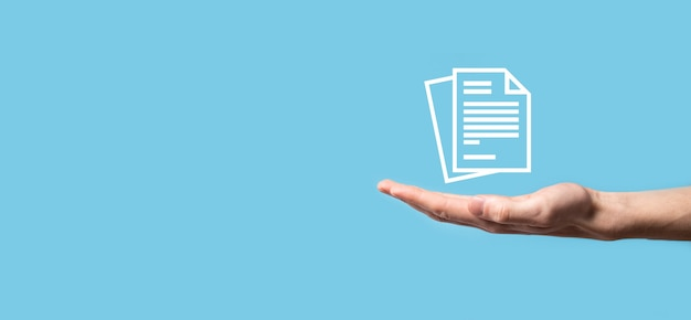 Mâle main tenant une icône de document sur fond bleu. système de données de gestion de documents business internet technology concept. système de gestion des données d'entreprise dms.