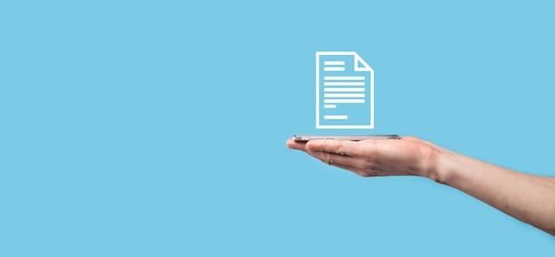Mâle main tenant une icône de document sur fond bleu. système de données de gestion de documents business internet technology concept. système de gestion de données d'entreprise dms.