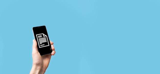 Mâle main tenant une icône de document sur fond bleu. système de données de gestion de documents concept de technologie internet d'entreprise. système de gestion des données d'entreprise dms