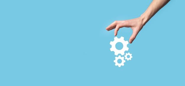 Mâle main tenant l'icône d'engrenages à crémaillère, icône de mécanisme sur les écrans virtuels sur fond bleu. concept d'entreprise de système de processus de technologie de logiciel d'automatisation. bannière.
