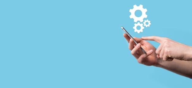 Mâle main tenant l'icône d'engrenages à crémaillère, icône de mécanisme sur les écrans virtuels sur la surface bleue