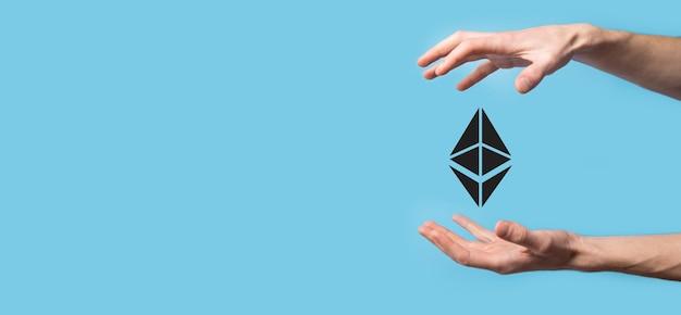 Mâle main tenant une icône ethereum sur la surface bleue