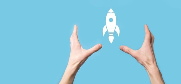 Mâle main tenant l'icône de fusée qui décolle, lancement sur une surface bleue