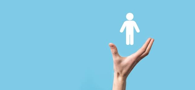 Mâle main tenant l'icône humaine sur fond bleu. ressources humaines gestion des ressources humaines recrutement emploi headhunting concept.sélectionnez le concept de chef d'équipe. mâle main cliquez sur l'icône de l'homme.bannière, copie spase.