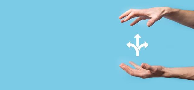 Mâle main tenant l'icône avec l'icône de trois directions sur fond bleu, aucun doute d'avoir à choisir entre trois choix différents indiqués par des flèches pointant en sens opposé concept de trois façons