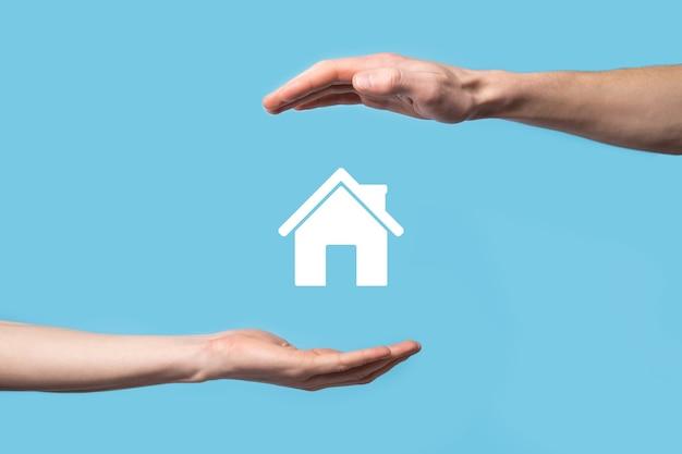 Mâle main tenant l'icône de la maison sur fond bleu.