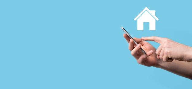 Mâle main tenant l'icône de la maison sur la surface bleue