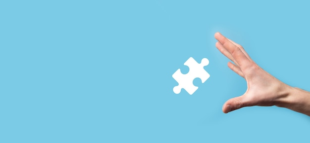 Mâle main tenant l'icône de puzzle sur la surface bleue