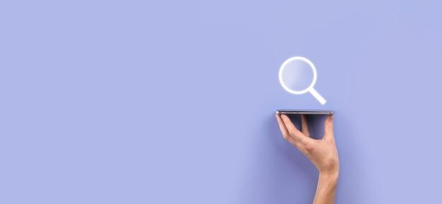 Mâle main tenant loupe, icône de recherche sur fond bleu. optimisation des moteurs de recherche de concept, support client. navigation sur les informations de données internet. concept de mise en réseau.