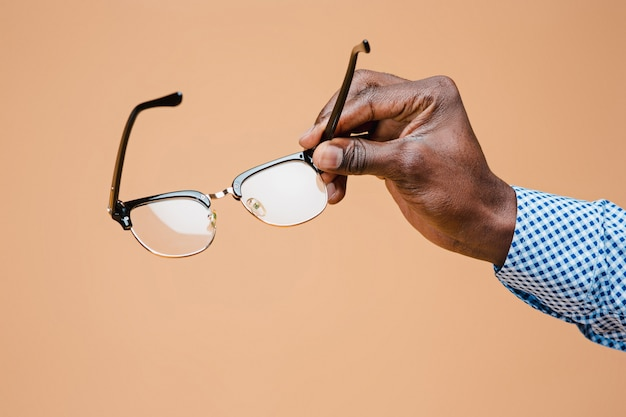 Mâle main tenant des lunettes, isolé