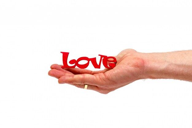 Mâle main tenant le mot d'amour en bois isolé. concept minimaliste.