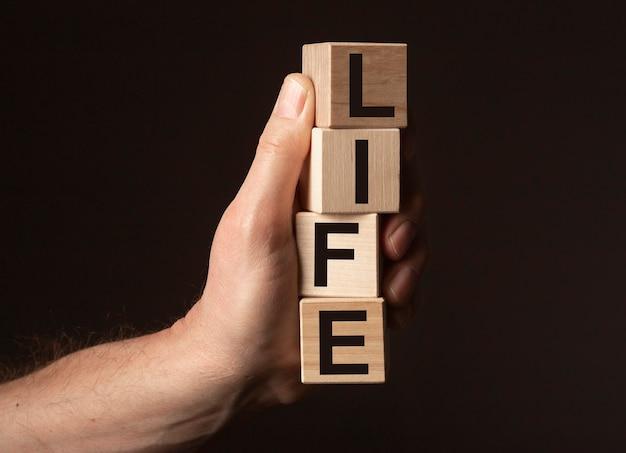 Mâle main tenant le mot de la vie sur des cubes en bois