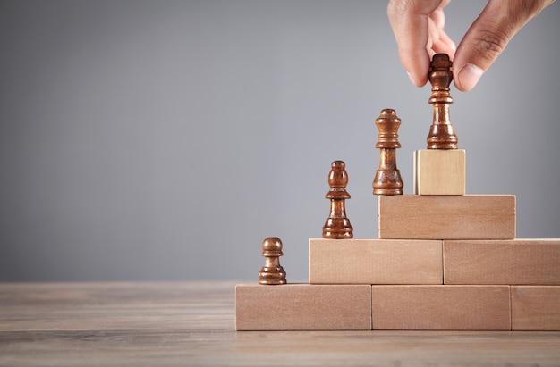 Mâle main tenant une pièce d'échecs sur des blocs de bois.